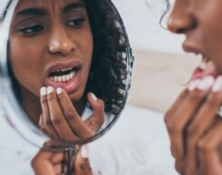 Woman Looking At Her Teeth In The Mirrow
